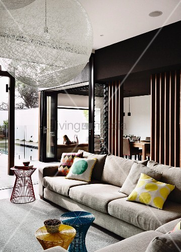 Beistelltische mit farbiger Verspannung vor Sofa, Raumteiler zum ...
