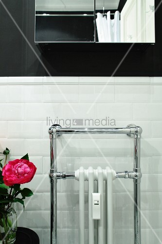 Radiator surrounded by towel rail against white-tiled bathroom wall