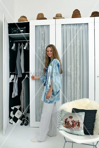 Young woman standing next to open wardrobe with curtains behind glass doors and hat moulds on top
