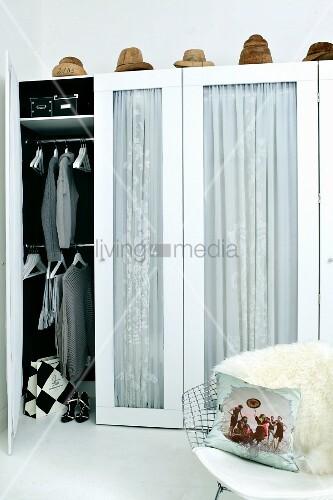 Kleiderschrank mit Glastüren und Vorhang, oberhalb Hutformen, im Vordergrund Klassikerstuhl mit Tierfell und Kissen