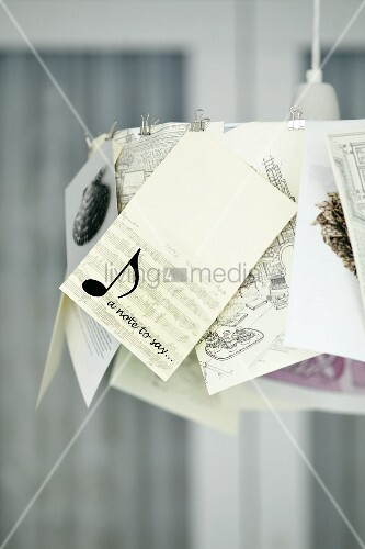 Pendant lamp with illustrations and cards clipped to lampshade