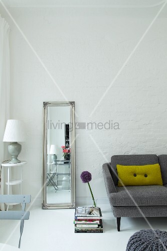 Full-length mirror leaning against whitewashed brick wall between lamp on side table and grey sofa