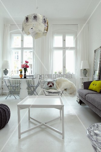 White side table on white-painted floor and seating area for two below window in modern interior