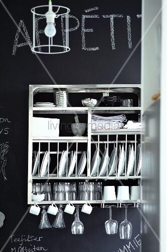 Stainless steel, wall-mounted crockery rack on chalkboard wall