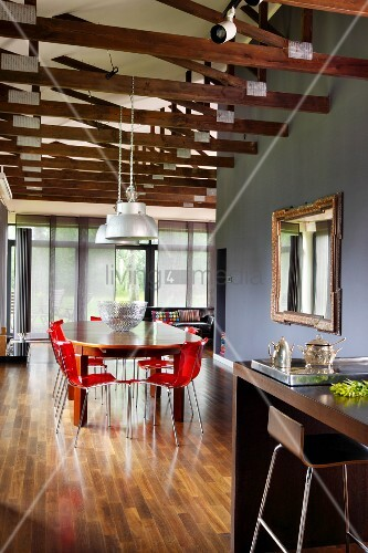 Open-plan interior with exposed wooden roof structure, counter and bar stool in foreground and dining area with red, plastic shell chairs in background