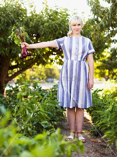 Blonde woman wearing striped dress holding freshly harvested beetroots