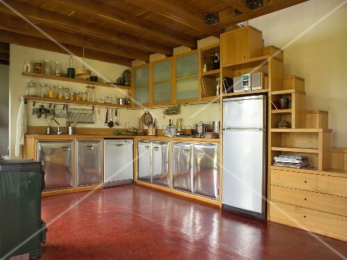 Kitchen area with curved stainless steel fronts and custom-made wooden cabinets with integrated samba staircase