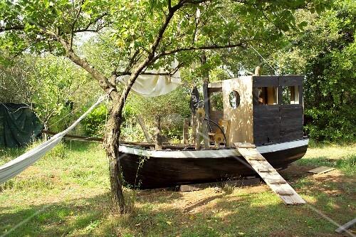 Wooden hut built on old boat in garden