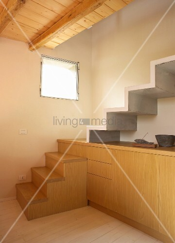 Block of stairs integrated into pale, wooden sideboard and continuing into concrete staircase