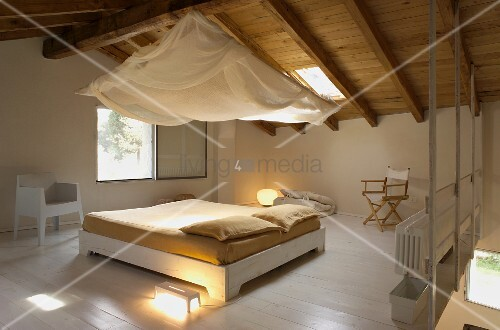 Free-standing double bed with pale wooden frame below canopy hanging from wooden ceiling in open-plan attic room