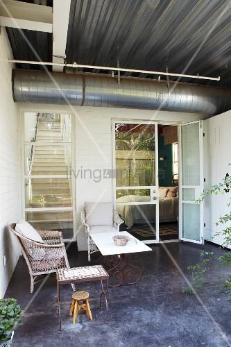 Möblierte Terrasse mit Rattanstuhl, Hocker und Tischen vor zeitgenössischem Wohnhaus, Lüftungsrohr unter Trapezblech Decke