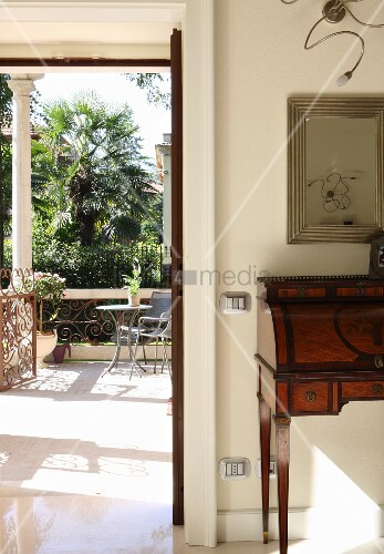 Delicate, antique bureau next to open door leading to villa terrace