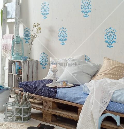 selbstgebautes tagesbett aus gestapelten holzpaletten polster und kissen vor wand mit. Black Bedroom Furniture Sets. Home Design Ideas