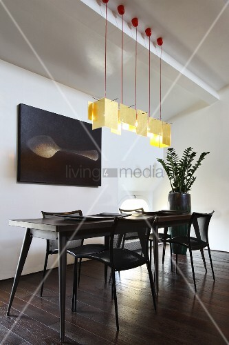 Designer-Esstisch mit Retro Flair und passenden schwarzen Stühlen unter Hängeleuchten-Reihe mit hellgelben Papier-Lampenschirmen