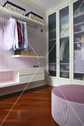 Shelves and purple and white striped wallpaper next to fitted wardrobe in dressing room with purple pouffe