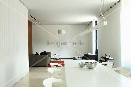 Moderner Essplatz in Weiss, im Hintergrund Loungeecke mit weisser Bogenlampe in offenem, minimalistischem Wohnraum