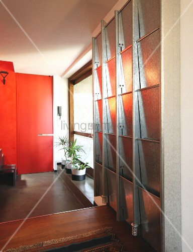 Metal cabinet with fold-down doors next to houseplants on windowsill; red door in background