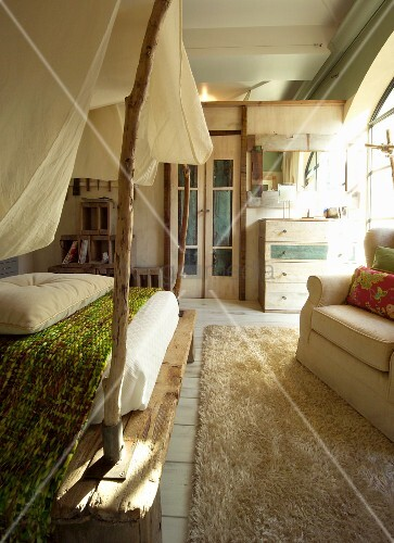 Rustic bedroom; four-poster bed with unfinished branches as posts and fabric canopy next to armchair on rug