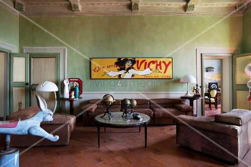 Yellow, vintage advertising sign on wall painted lime green and sofa set in Italian, Renaissance period apartment
