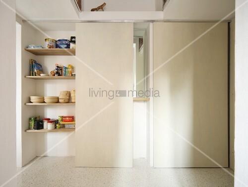 Pantry hidden behind white sliding doors in corridor