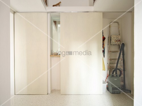 Storage space for bulky household appliances hidden behind unobtrusive, white sliding doors in corridor
