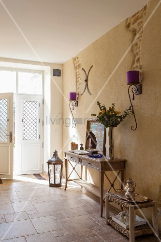 An elegant, traditional entranceway with a wall table and wrought iron wall lamps with purple lampshades