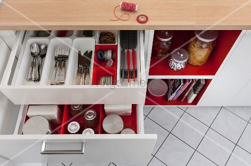 Blick auf geöffnete Schubladen im Küchenschrank, rote und weisse ...