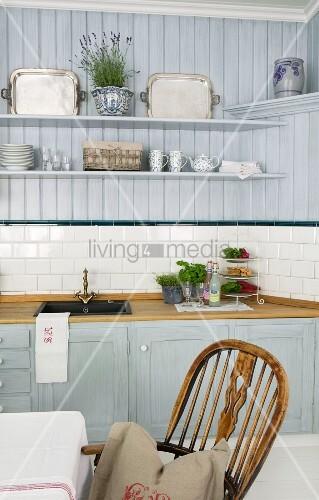 Pastellblaue Landhausküche mit dekorierten Wandborden; Windsor-Stuhl am Esstisch im Vordergrund