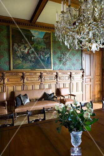 Crystal chandelier above table with Biedermeier chairs in dining room of grand country house with leather sofa set below oil painting in background