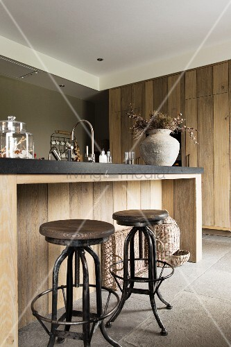Vintage bar stools at island counter with black worksurface and solid-wood front
