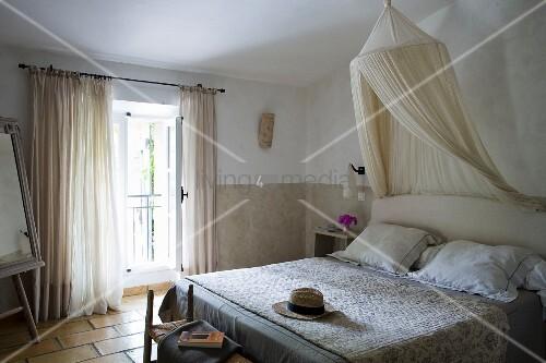 Weiche Naturfarben in Gästezimmer provenzalischen Stils mit Moskitonetz und gestepptem Überwurf (Boutis) auf Doppelbett