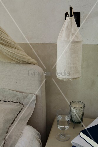 Leinensack als Schirm einer Wandleuchte über Nachttisch neben Bett mit Kopfteil vor halbhoch getönter Wand