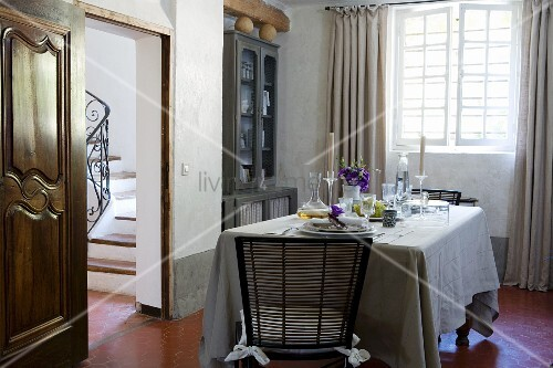 Gedeckter Tisch in provenzalischem Esszimmer mit weissem Kalkanstrich