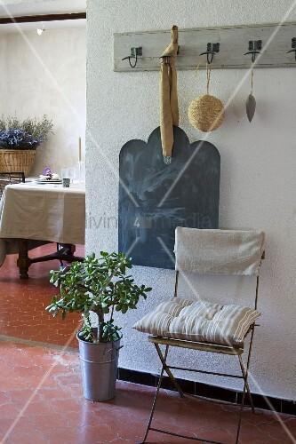 Gartenstuhl mit Kissen und Pfennigbaum unter alter Garderobenleiste mit aufgehängter Schreibtafel, Esstisch im Hintergrund