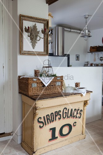 Vintage cabinet and wicker hamper next to white, half-height wall; stainless steel extractor hood in kitchen in background