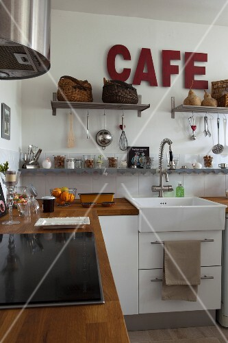 Wooden worksurfaces, white base units, cooking utensils on wall-mounted shelves and dark red lettering on wall in country-house-style kitchen