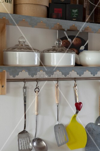 Cooking utensils hung below wall-mounted shelves with zinc edging