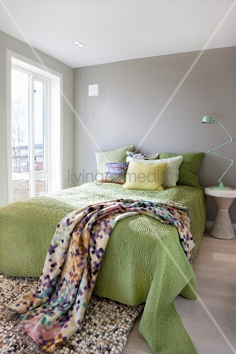 Green bedspread and scatter cushions arranged on double bed and classic table lamp on bedside table in bedroom painted pale grey