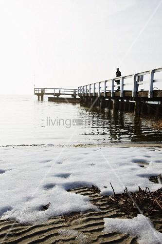 Seeufer mit Schnee bedeckt, im Hintergrund Mensch auf Holzsteg
