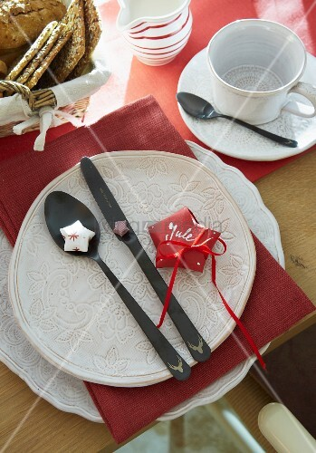 A folded red paper as a place card on a white plate with cutlery next to a cup and saucer