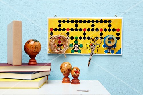 Creative pin board made from board game collage for storing scissors, sticky tape and twine