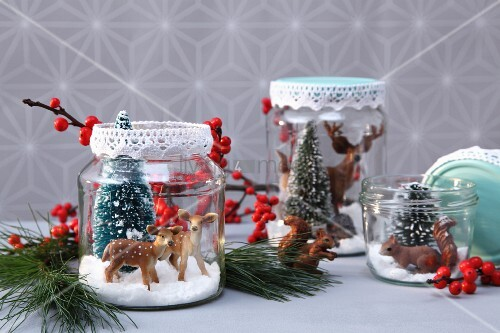 Plastiktiere und -tannen mit Kunstschnee in Konservengläsern, Deckel verziert mit Spitzenborte als weihnachtliche DIY-Deko
