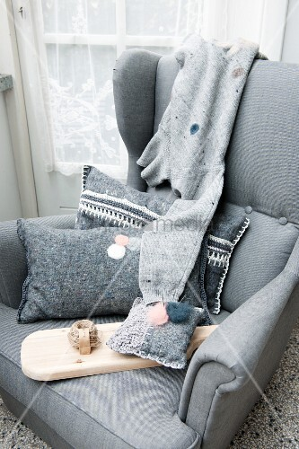 Felt scatter cushions, one embroidered, pin cushion and reel of thread on wooden board on grey armchair