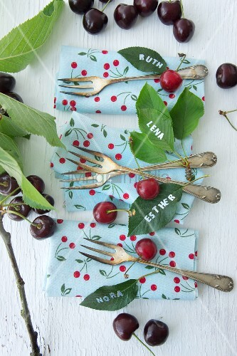 Cherries, napkins, cake forks and names written on cherry leaves