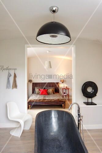 Freistehende Badewanne in Grau mit Standarmatur in minimalistischem Bad, weisser Klassikerstuhl neben Durchgang und Blick auf Doppelbett mit ländlichem Flair