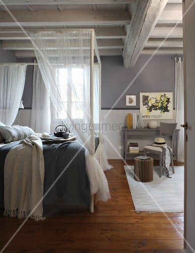 Rustic bedroom with grey-painted walls and four-poster bed with translucent curtains below white, wood-beamed ceiling