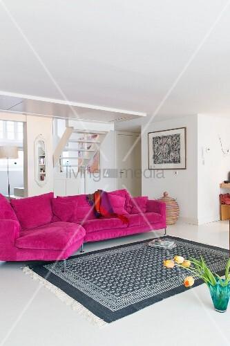 Weiss-grau gemusterter Teppich vor Magenta Couch in hellem ...