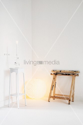 White interior: two painters' trestles leaning against wall next to spherical lamp and plant stand