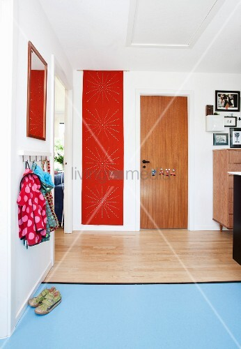 Hallway with children's coat rack, wooden flooring and pale blue lino flooring and red perforated flag hung on wall in background