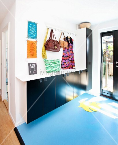 Foyer with pale blue lino floor, floating cupboards with black doors and bags hung from row of hooks on wall